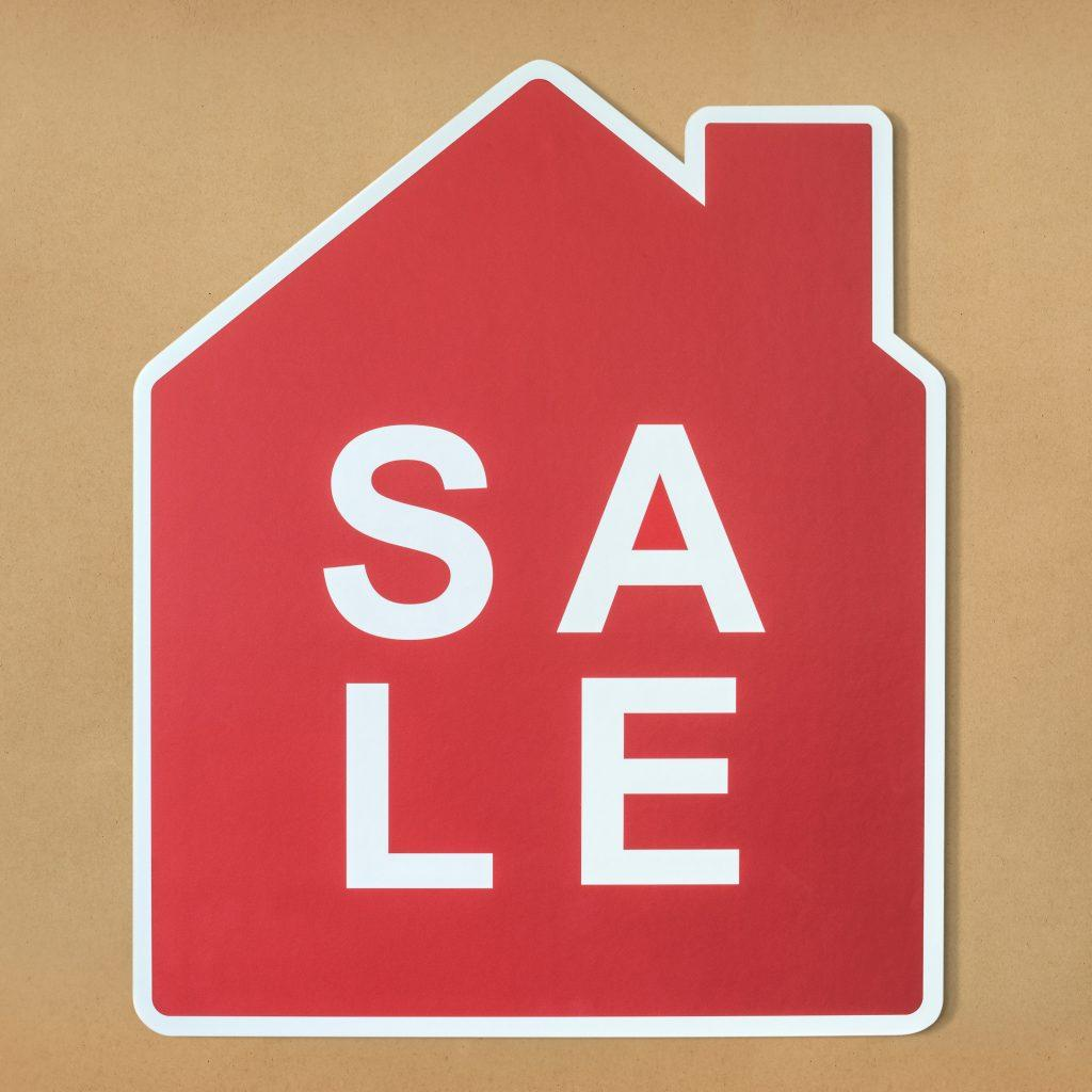 "A house-shaped sticker with the word ""SALE"" printed on it."
